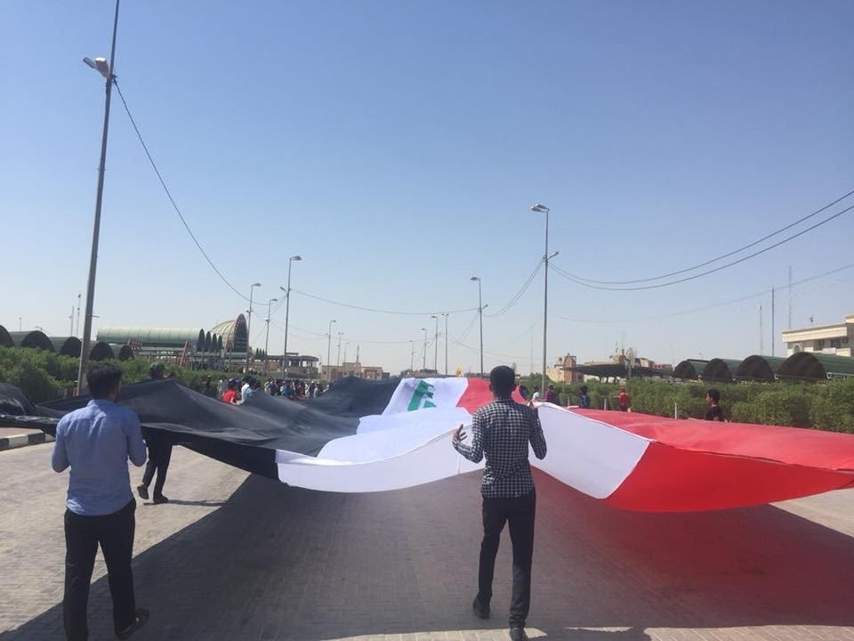بالصور.. متظاهرو المثنى يرفعون أطول علم عراقي