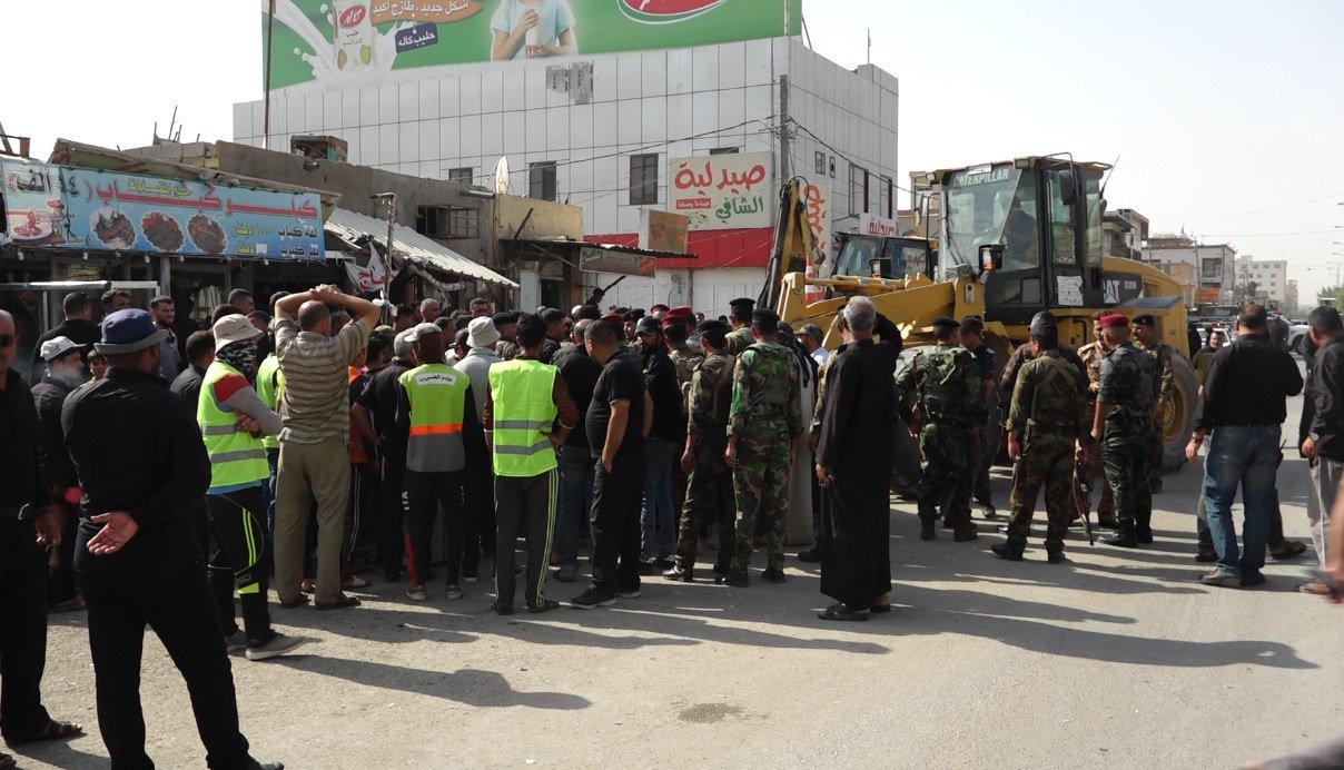 بالصور.. مواطنون يمنعون آليات بلدية كربلاء من تهديم سوق الحبوبي